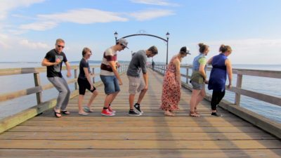 Image: people dancing on a boardwalk