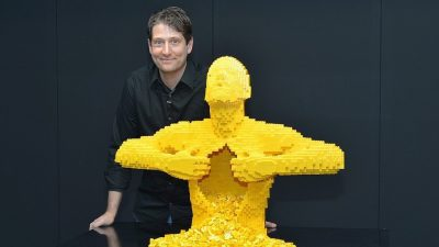 Image: Lego Artist Nathan Sawaya with Yellow man a sculpture made of Legos
