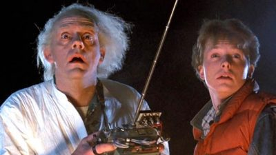 Image: Two men looking off into the distance. One has white hair poking out into all directions and is wearing a labcoat. He's holding a remote. The other is younger, wearing a red vest.