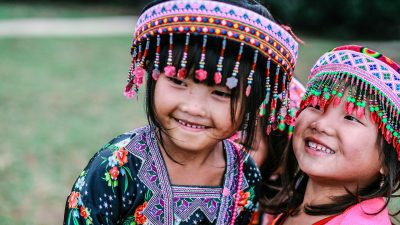 Image: Two girls smiling and wearing traditional hats