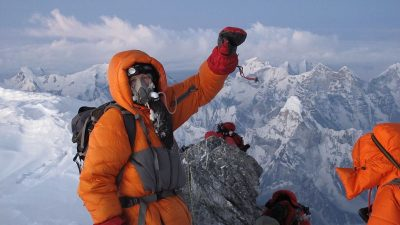 Image: Climber in victory pose at the top of Mt. Everest