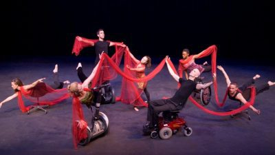 Image: mixed ability dancers dancing together onstage some in early versions of the Rolling Dance Chair a new wheelchair technology