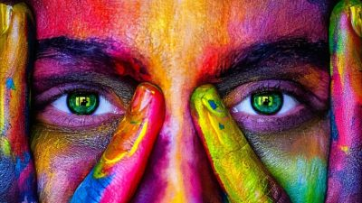 Image: Womans face painted in colors. Eyes peeking through fingers.