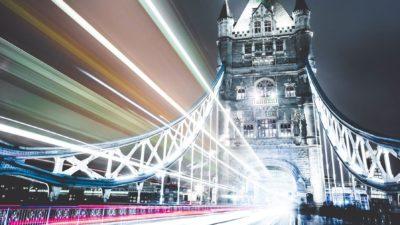 Image: London bridge at night with lights moving through it