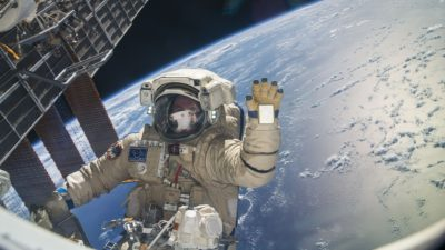 Image: Astronaut waving at camera above earth