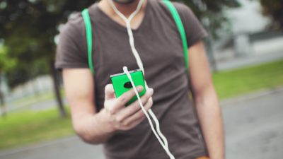 Image: Man walking and listening to music on his smartphone through headphones