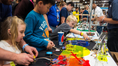 Image: Kids Learning to control a toy robotic arm at a Maker Faire