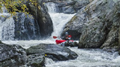 Image: Kayaker paddling down a river with rapids and a waterfall behind them